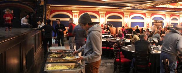 Un homme se sert de la nourriture alors qu'on voit en arrière-plan la scène et une partie de la salle du Théâtre Rialto
